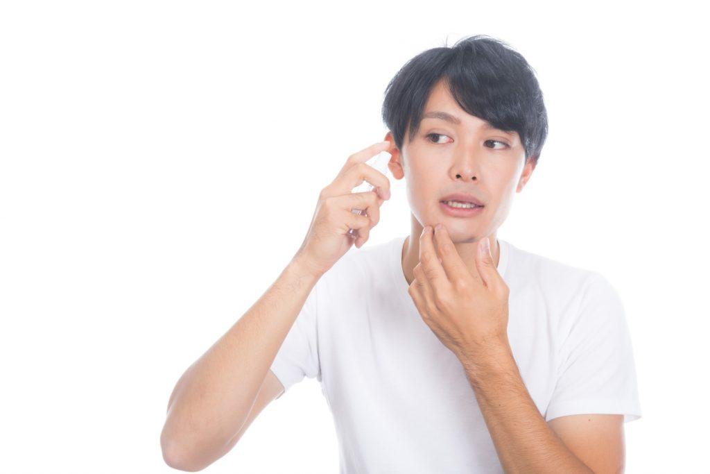 化粧水をかける男性